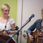 From left, Jordan Wallace, a biology senior at Brenau, laughs alongside her bandmate Carly Burruss, a student at Kennesaw State University, as they play with their band, The Sawnee Mountain Train Wreck, during the Bluegrass and Books event at the Brenau University Tea Room.